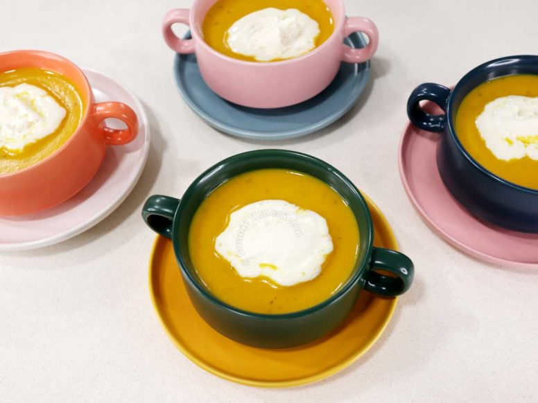 Four bowls of squash soup topped with whipped cream
