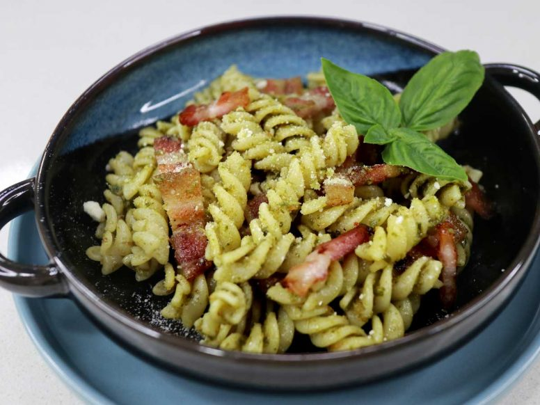 Bacon pesto pasta garnished with Parmesan and a sprig of basil