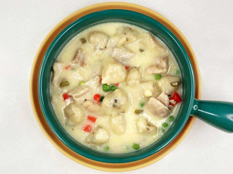 Chicken and Dumplings in Green Bowl Set on Yellow Plate