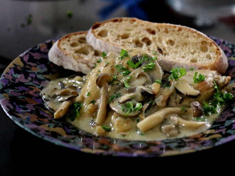 A serving of Chicken Mushrooms Casserole with bread on the side