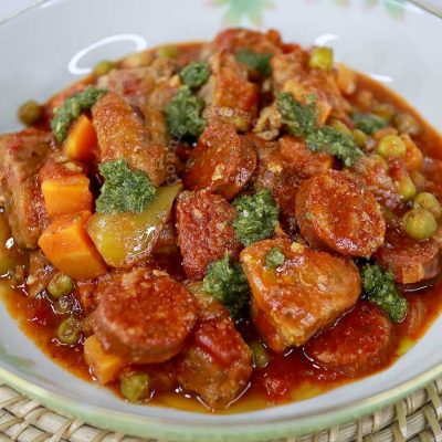 Pork and sausage stew garnished with dollops of pesto