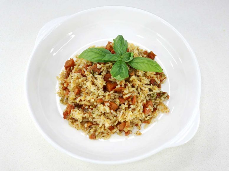 Spicy sausage and pesto rice in shallow white bowl