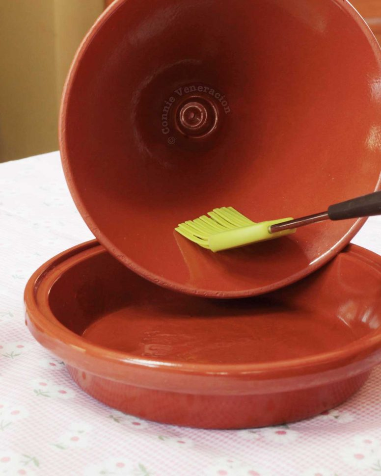 Brushing the inside of the conical cover of a tajine with oil