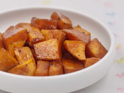 Baked brown sugar-glazed sweet potatoes in small shallow bowl
