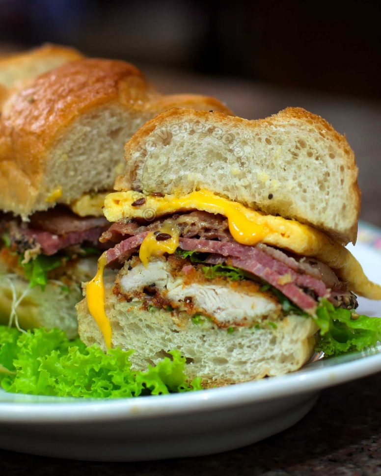 Cross cut of carnivore's dream sandwich with chicken, beef, pork and egg filling