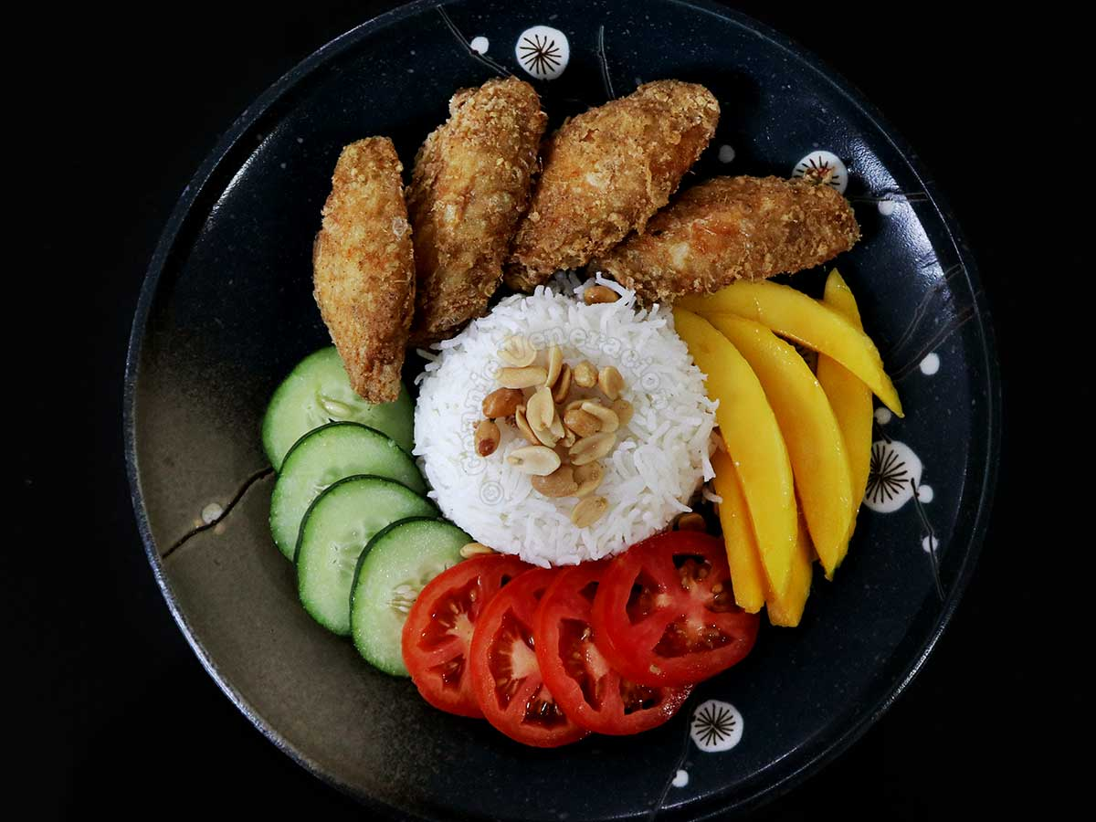 Rice, fried chicken, mangoes, cucumber and tomato slices
