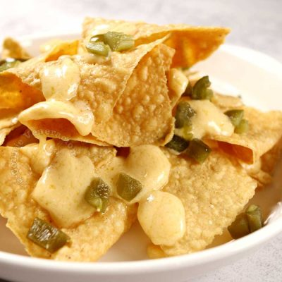 Nachos with cheese sauce and pickled japapeños
