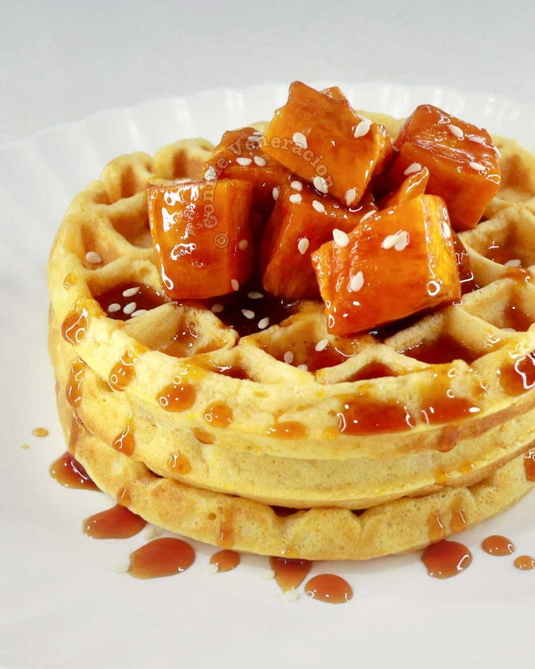 A stack of sweet potato waffles with candied sweet potatoes as topping