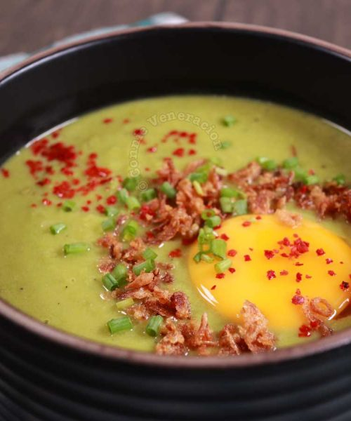 Fresh pea soup topped with an egg yolk, fried shallots, chili flakes and scallions