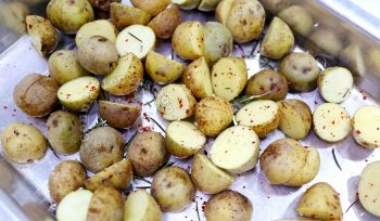 Halved baby potatoes tossed with rosemary, salt and chili