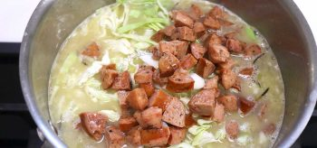 Simmering pureed chickpeas, sausages and cabbage in pot