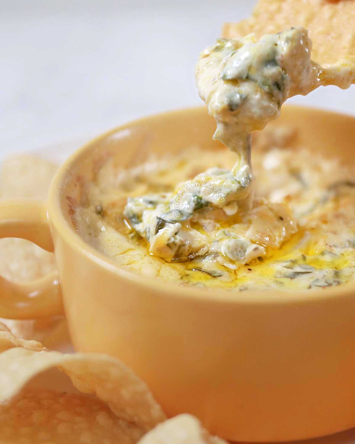 Scooping spinach artichoke dip with tortilla chip