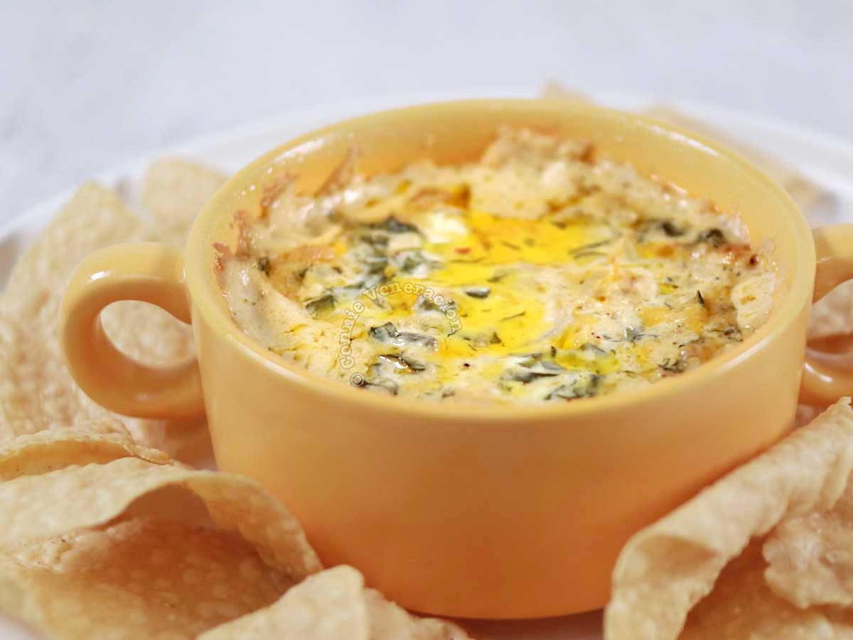 Spinach artichoke dip surrounded by tortilla chips