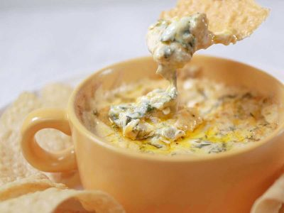 Spinach artichoke dip in yellow bowl