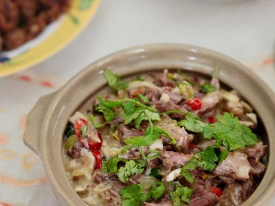 Spicy Beef and Coconut Stew Garnished with Sliced Chilies and Cilantro