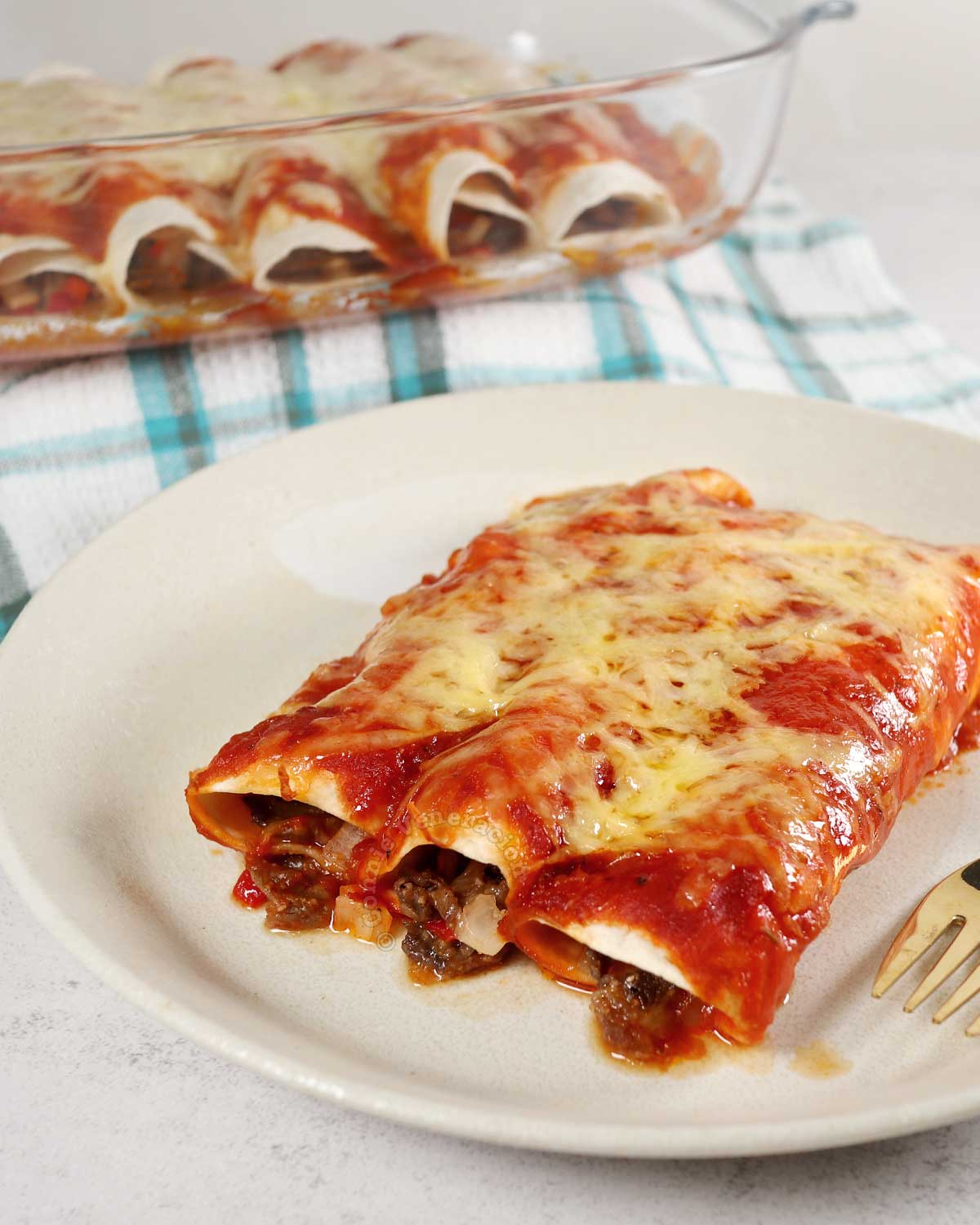 Beef enchiladas on a plate and a tray of more beef enchiladas in background