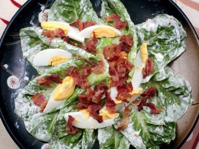 A salad of Romaine lettuce, wedges of hard-boiled egg and crumbled crispy bacon